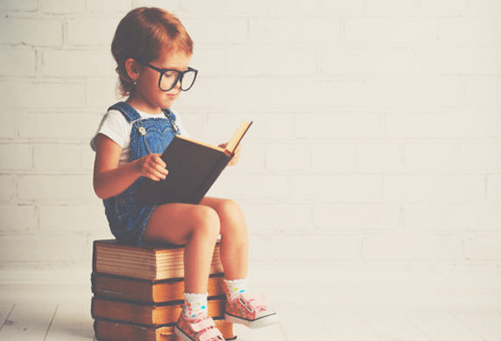 child reading while sitting on books